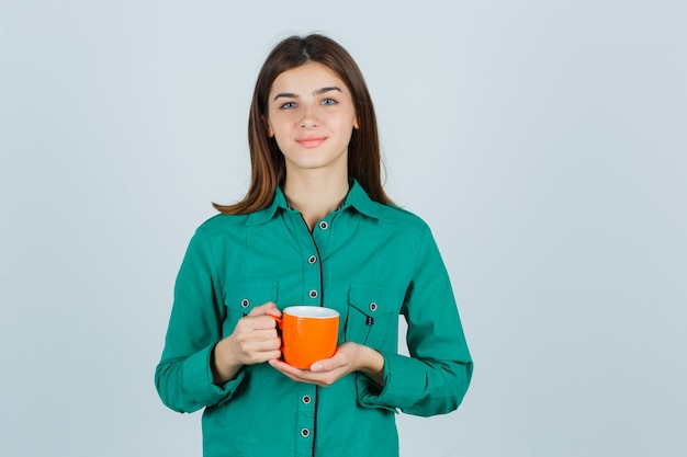 Giovane signora che tiene tazza arancione di tè in camicia e che sembra pacifica. vista frontale.