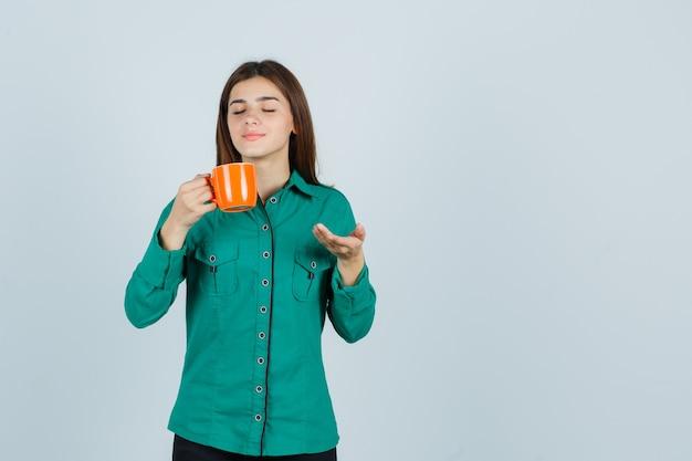 Giovane signora che tiene una tazza di tè arancione, mostrando qualcosa in camicia e guardando pacifica. vista frontale.