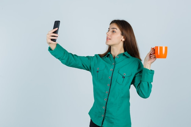 Young lady holding orange cup of tea, taking selfie with mobile phone in shirt and looking confident. front view.