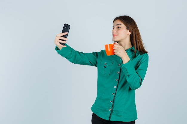Young lady holding orange cup of tea, taking selfie with mobile phone in shirt and looking confident , front view.