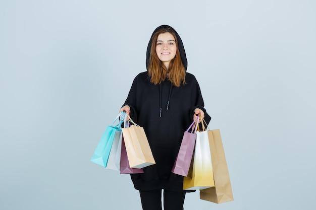 Giovane donna che tiene i pacchetti mentre guarda la telecamera in felpa con cappuccio oversize, pantaloni e sembra felice. vista frontale.