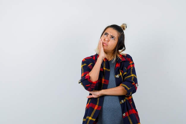 Young lady holding palm on cheek in casual checked shirt and looking puzzled , front view.