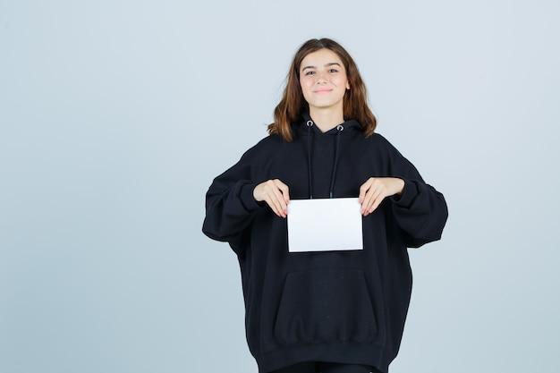 Giovane donna che tiene carta davanti a lei in felpa con cappuccio oversize, pantaloni e sembra felice, vista frontale.