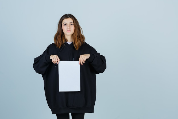 Young lady holding paper in oversized hoodie, pants and looking confident. front view.