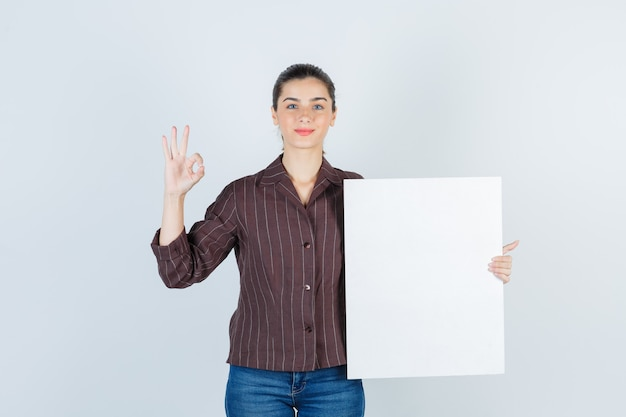 紙のポスターを持っている若い女性、シャツ、ジーンズで大丈夫なジェスチャーを示し、自信を持って、正面図を表示します。