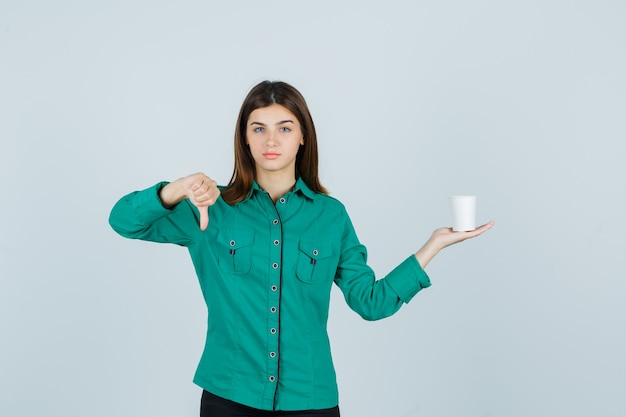 Young lady holding plastic cup of coffee while showing thumb down in shirt and looking dissatisfied , front view.