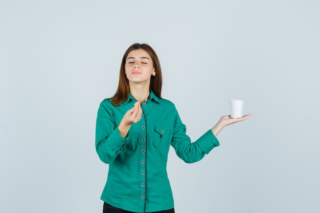 셔츠에 맛있는 제스처를 표시하고 기쁘게 찾고있는 동안 커피의 플라스틱 컵을 들고 젊은 아가씨, 전면보기.