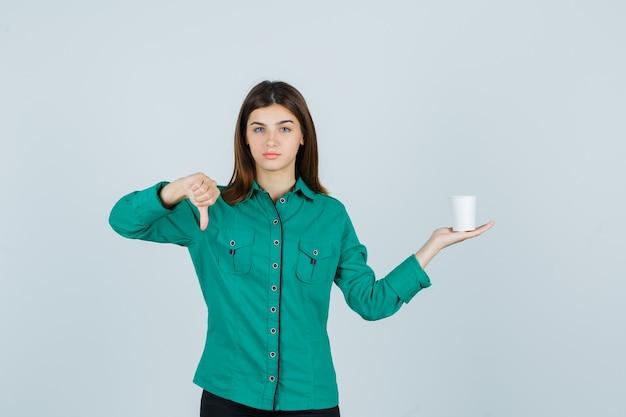 셔츠에 아래로 엄지 손가락을 표시하고 불만족, 전면보기를 찾고있는 동안 커피의 플라스틱 컵을 들고 젊은 아가씨.