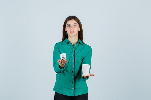 Молодая леди держит пластиковые чашки кофе в рубашке и выглядит уверенно, вид спереди.