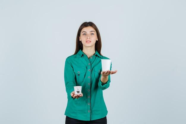 シャツにプラスチック製のコーヒーカップを保持し、自信を持って、正面図を探している若い女性。