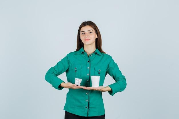 シャツにプラスチック製のコーヒーカップを保持し、満足している、正面図を探している若い女性。