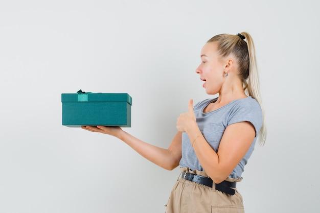 プレゼントボックスを持って、tシャツとズボンで親指を表示し、幸せそうに見える若い女性
