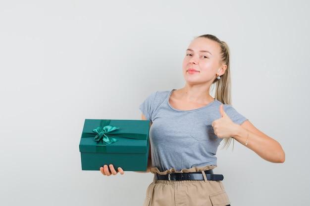 プレゼントボックスを持って、tシャツとズボンで親指を見せて、うれしそうに見える若い女性