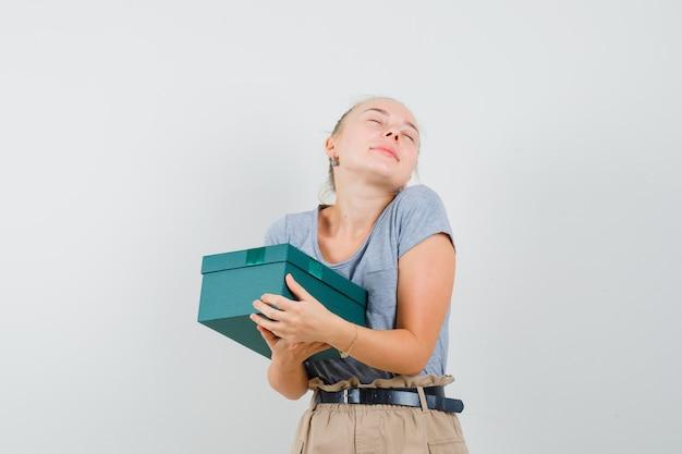 Giovane donna che tiene la casella attuale in maglietta e pantaloni e sembra allegra
