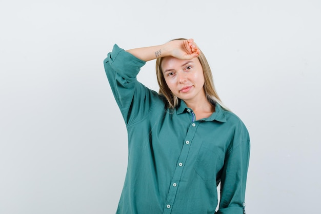 Young lady holding raised hand on head in green shirt and looking delicate.