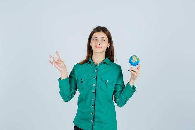 Giovane donna che tiene un piccolo globo terrestre, che mostra il numero dieci in camicia e sembra soddisfatto, vista frontale.