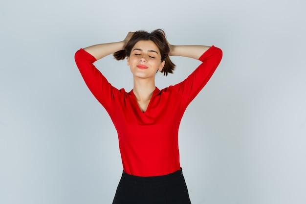 Giovane donna che tiene una ciocca di capelli in camicetta rossa, gonna e sembra carina