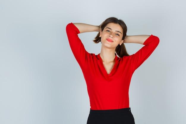 Молодая леди держит прядь волос в красной блузке, юбке и выглядит весело