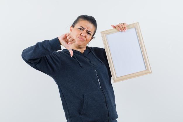 Молодая леди держит белую пустую рамку, показывая большой палец в куртке и выглядит недовольным