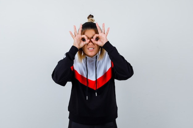 Giovane donna in felpa con cappuccio che mostra il gesto degli occhiali e sembra divertita