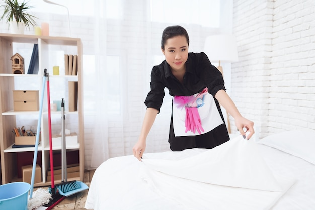 Young lady housekeeper arranges bed in hotel.