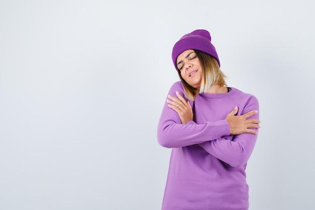 Giovane donna che si abbraccia in maglione viola, berretto e sembra pacifica. vista frontale.
