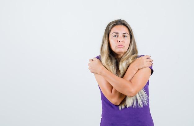 Giovane donna che si abbraccia in maglietta viola e sembra triste, vista frontale.