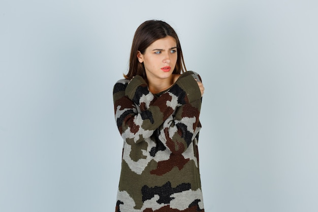 Young lady hugging herself while feeling cold in sweater, skirt and looking displeased