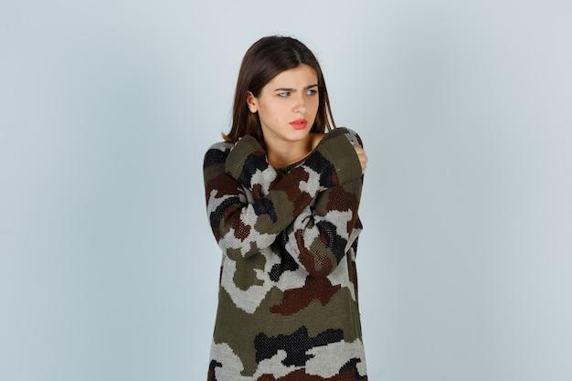 Giovane donna che si abbraccia mentre si sente freddo in maglione, gonna e sembra dispiaciuta