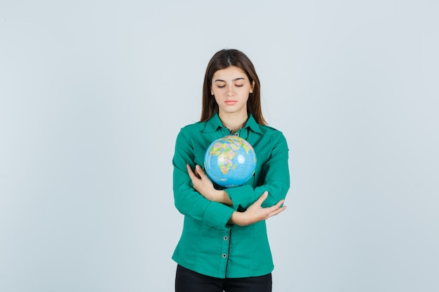 Young lady hugging terrestrial globe in shirt and looking careful , front view.