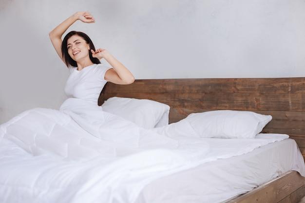 Девушка в белом топе сидит на кровати, покрытой белым бельем, и улыбается, растягиваясь по утрам