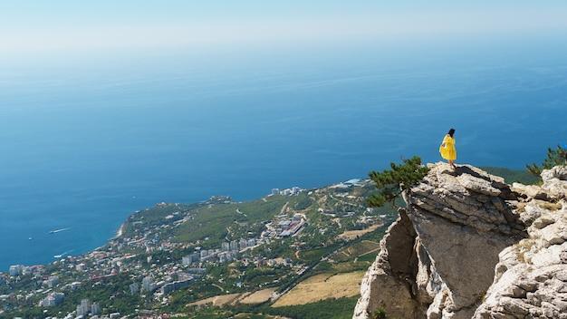 青い海のそばの街を背景に、黄色いドレスを着た若い女性が岩の上に立っています。ロマンチックなコンセプト。