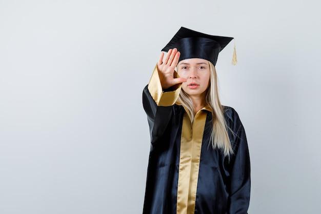 Молодая дама в академической одежде показывает жест стоп и выглядит встревоженной