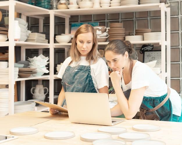 テーブルに立って学生を教えるエプロンの若い女性