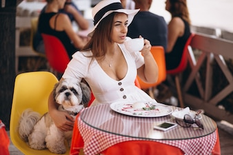 Young lady in bar with cute dog having lunch