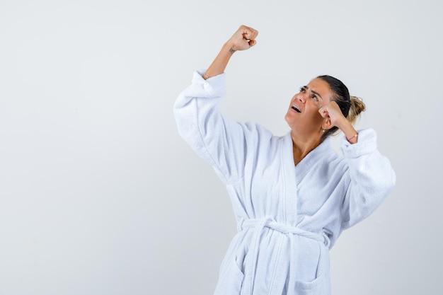 Молодая дама в халате показывает жест победителя и выглядит удачливой