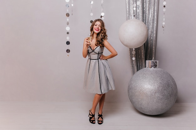 아름다운 디자이너 드레스와 발 뒤꿈치가있는 검은 신발에 젊은 아가씨, 크리스마스 장식에 대한 흰색 스파클링 와인 한 잔과 함께 포즈