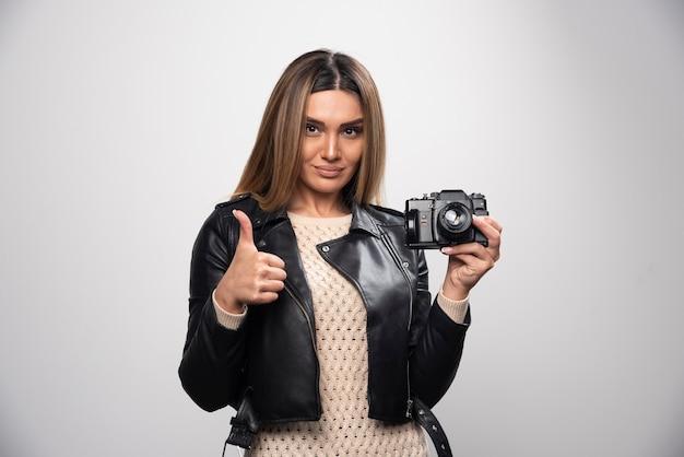 Молодая дама в черной кожаной куртке позитивно и улыбаясь фотографирует с камерой