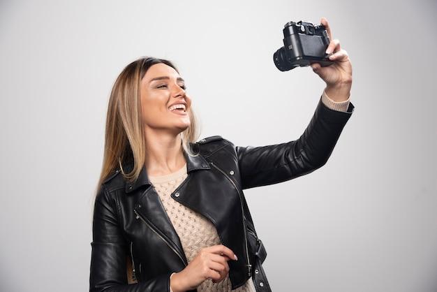 긍정적이고 웃는 방식으로 카메라로 사진을 찍는 검은 가죽 재킷에 젊은 아가씨