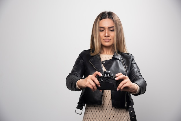 진지하고 전문적인 방식으로 카메라로 사진을 찍는 검은 가죽 재킷에 젊은 아가씨