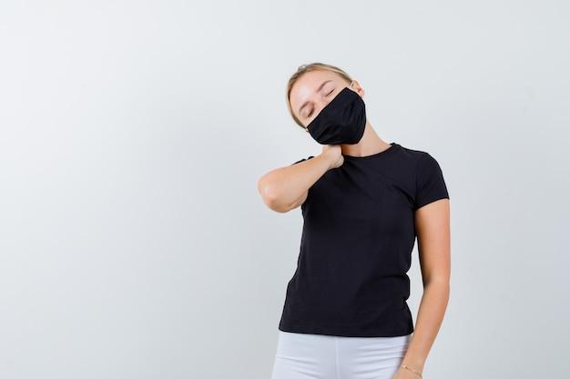 검은 색 티셔츠에 젊은 아가씨, 목 통증으로 고통 받고 피곤해 보이는 마스크, 전면보기.
