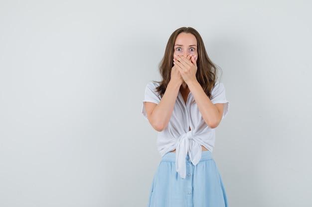 ブラウスとスカートの若い女性が口に手をつないで、物欲しそうに見える