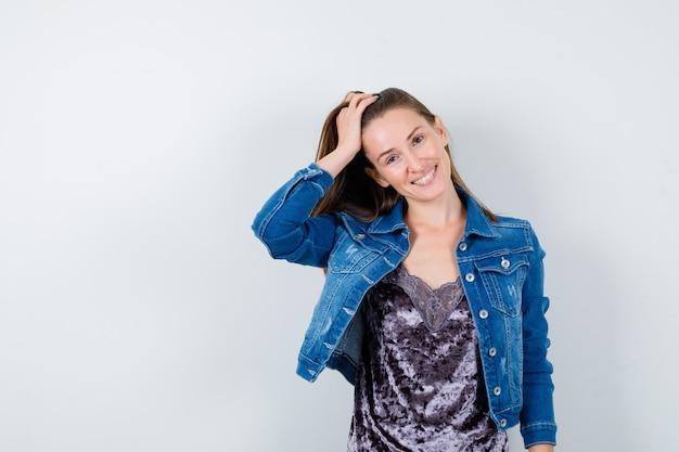 ブラウスの若い女性、デニムジャケットは手で髪をとかし、陽気に見える、正面図。
