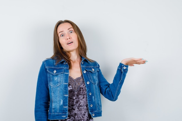 ブラウスの若い女性、何かを持って困惑しているデニムジャケット、正面図。