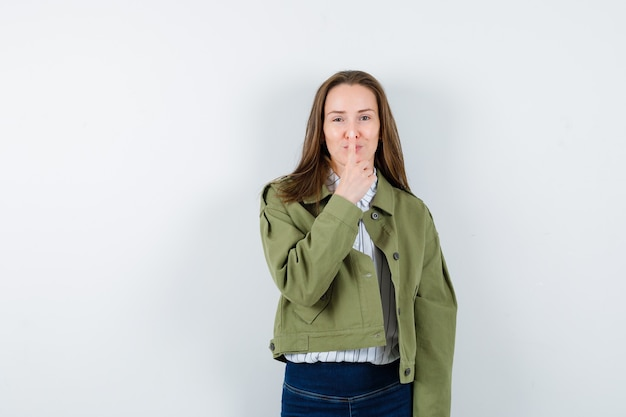 Молодая дама в блузке держит палец на носу и хорошо выглядит, вид спереди.