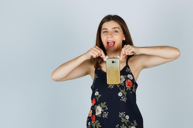 Молодая дама в блузке держит смартфон и выглядит счастливым, вид спереди.