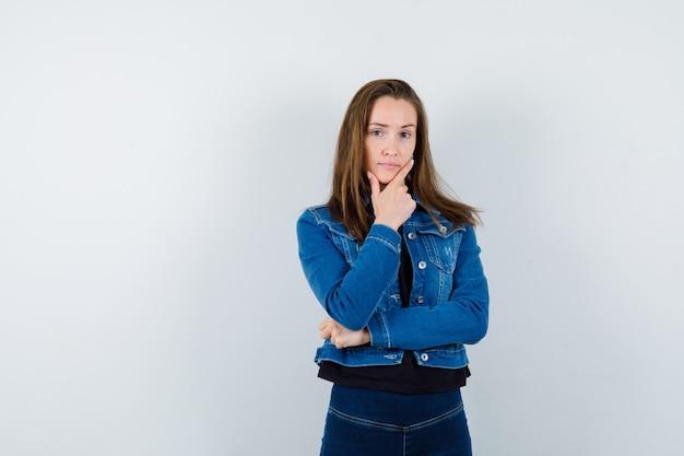 ブラウス、ジャケット、ジーンズを着た若い女性が、賢明な正面図を考えて見ながらあごを持っています。
