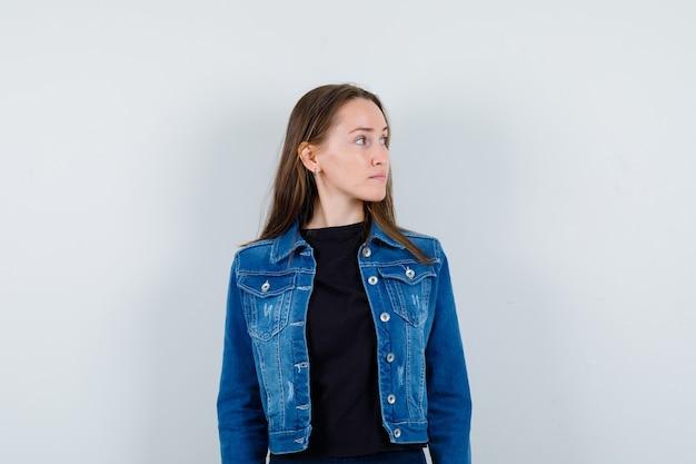 ブラウスを着た若い女性、脇を向いて落ち着いて見えるジャケット、正面図。