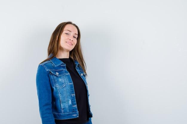 Молодая дама в блузке, куртке, глядя в камеру и уверенно глядя, вид спереди.