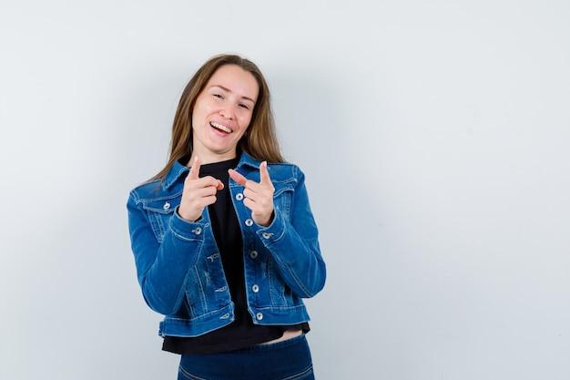 Молодая дама в блузке, куртке, указывая на камеру и уверенно глядя, вид спереди.